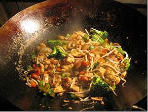 "stir fry cook in 16"" wok held by the spider in large big green egg"
